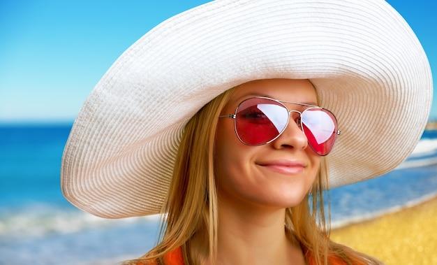 Привлекательная женщина в шляпе, отдыхая на пляже