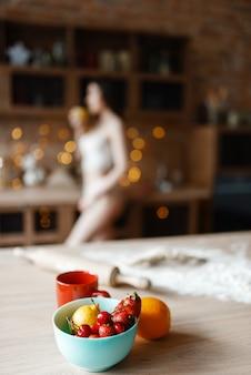 キッチンで調理するレースのランジェリーで魅力的な女性。裸の女性の人が自宅で朝食を準備、衣服なしの食事の準備