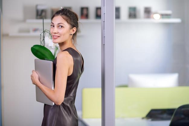 Привлекательная женщина в кожаном платье, улыбаясь, держа ноутбук