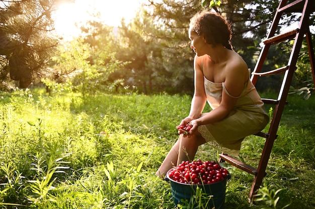さくらんぼのバケツの横にある脚立に座っているリネンのドレスを着た魅力的な女性