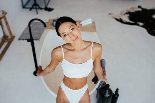 お風呂の近くでポーズをとるランジェリーの魅力的な女性。カメラにポーズをとる女の子