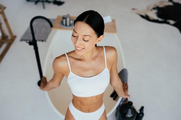 목욕 근처 포즈 란제리에서 매력적인 여자. 카메라에 포즈를 취하는 여자