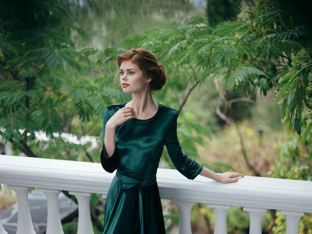 豪華な緑のドレスの緑の葉の魅力的な女性は、自然のロマンス建築を残します。