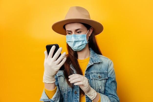 医療の滅菌フェイスマスク手袋で魅力的な女性は、ソーシャルメディアをチェックするアプリで買い物に携帯電話を保持している黄色の背景に分離されたデニムジャケットと帽子を着ています。人混みを避ける