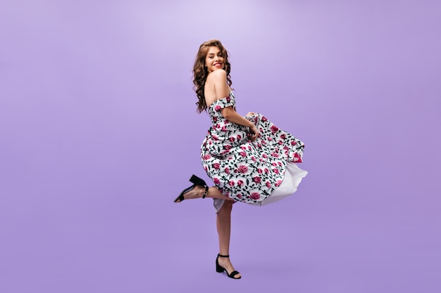 ミディドレスの魅力的な女性は紫色の背景で踊ります。花の服と黒い靴の笑顔で素晴らしい巻き毛の女の子。