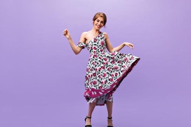 孤立した背景で踊るミディドレスの魅力的な女性。孤立した背景で踊るミディドレスの魅力的な女性。