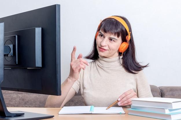 Привлекательная женщина в оранжевых наушниках сидит за столом с книгами, глядя на монитор компьютера и поднимая палец вверх