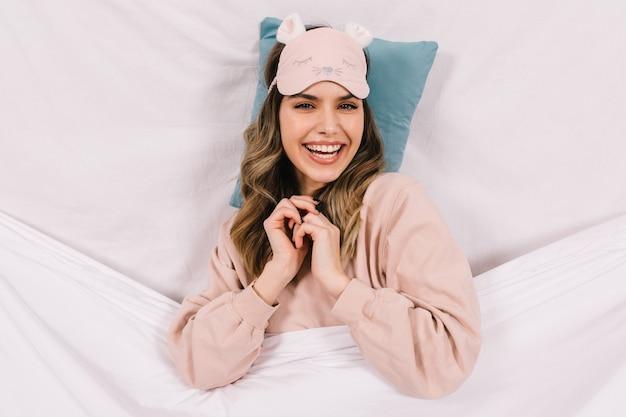 Привлекательная женщина в розовой маске сна позирует в постели