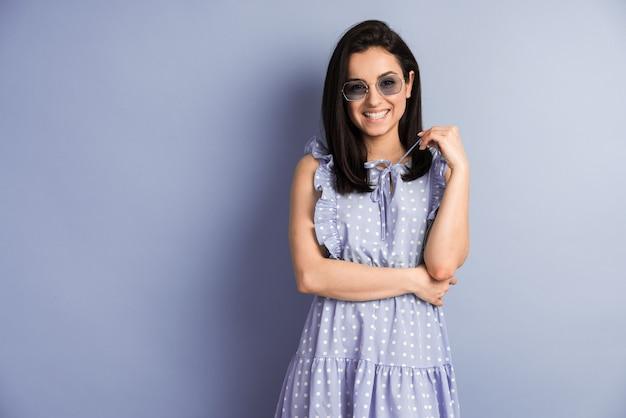 행복 한 얼굴로 보라색 벽에 서있는 폴카 도트 드레스에 매력적인 여자