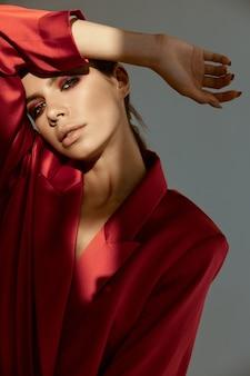 赤いジャケットの魅力的な女性が頭に手を握って光が顔に落ちる