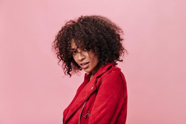 Привлекательная женщина в красном наряде смотрит в камеру на изолированной стене
