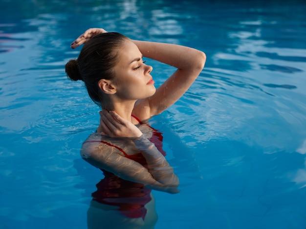 赤い水着の魅力的な女性は、澄んだプールの水でトリミングされたビューで泳ぎます。高品質の写真