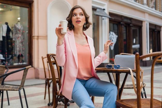분홍색 재킷, 세련된 의류를 입고 테이블에 앉아 행복에 미소 짓는 낭만 분위기의 매력적인 여자, 카페에서 데이트하는 남자 친구를 기다리고, 카푸치노를 마시고, 얼굴 표현을 종료했습니다.