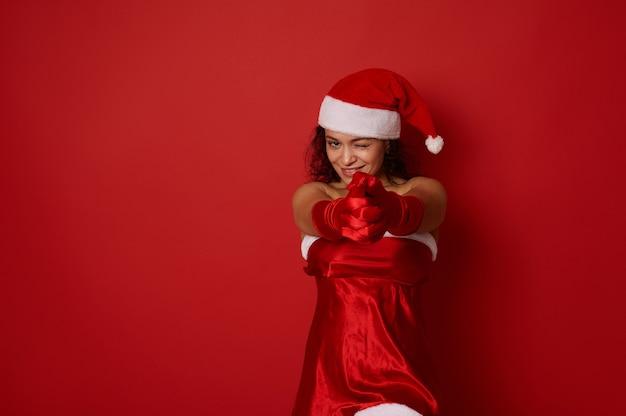 산타 카니발 의상을 입은 매력적인 여성이 손을 잡고, 촬영을 하고, 카메라에 똑바로 미소를 짓고, 광고를 위한 복사 공간이 있는 빨간색 배경에 포즈를 취합니다. 새 해와 크리스마스 개념