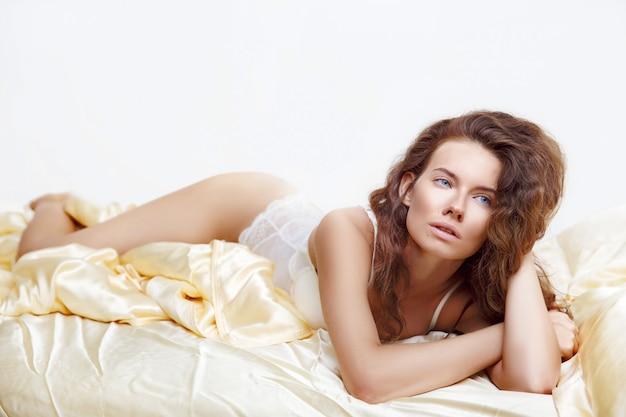 침대에 매혹적인 포즈에 누워 섹시한 흰색 란제리에 매력적인 여자