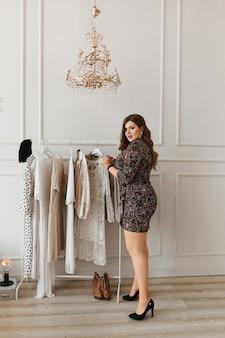 Привлекательная женщина в коротком платье, выбирая наряд на дому