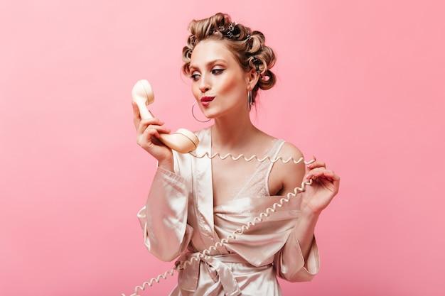 실크 집에 옷을 입은 매력적인 여자가 전화 송수화기를 바라보고 분홍색 벽에 포즈를 취합니다.
