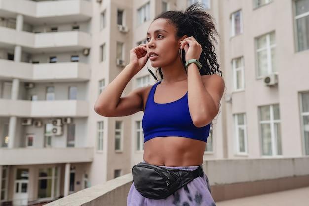 屋上でスポーツフィットネスの都会的な衣装でワークアウトを作る魅力的な女性