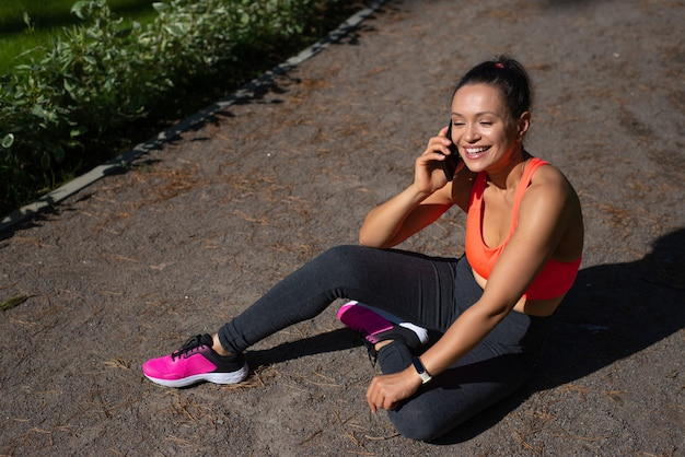 ランニングや屋外でのトレーニング後にリラクゼーションを楽しむスポーツウェアの魅力的な女性