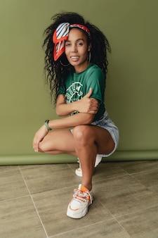 緑のスタジオの壁にスタイリッシュな流行に敏感な衣装のtシャツとショートパンツの魅力的な女性