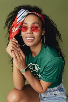 녹색 스튜디오 벽에 세련된 힙스터 복장 티셔츠와 반바지를 입은 매력적인 여성