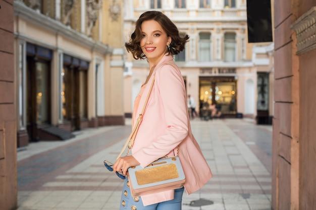 Привлекательная женщина в стильном наряде гуляет по городу, уличная мода, весенне-летний тренд, улыбающееся счастливое настроение, в розовой куртке и блузке, кружится, вышла, модница за покупками