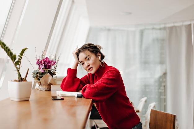 スタイリッシュな赤い服を着た魅力的な女性がテーブルに寄りかかった