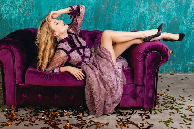 벨벳 소파에 누워 세련된 보라색 레이스 이브닝 드레스에 매력적인 여자