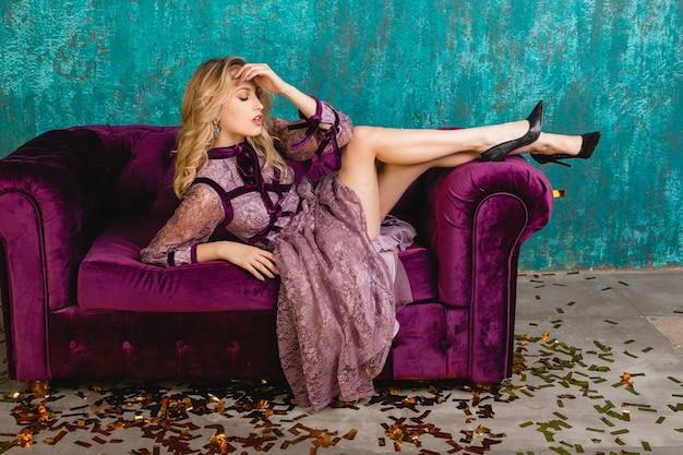 Привлекательная женщина в стильном фиолетовом кружевном вечернем платье, лежа на бархатном диване