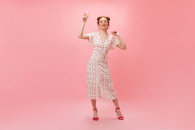 Привлекательная женщина в стильном белом платье в горошек танцует с бокалом шампанского на розовом фоне.