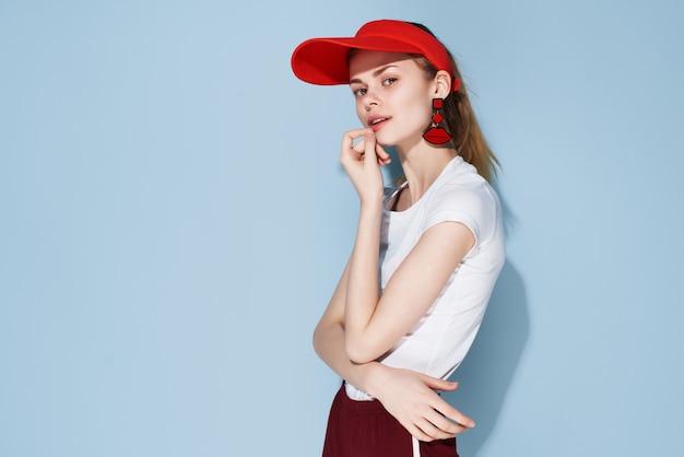 Привлекательная женщина в летней одежде красная кепка синем фоне