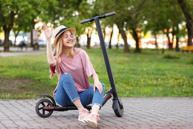 산책을위한 전자 스쿠터와 함께 여름에 매력적인 여자를 환영합니다