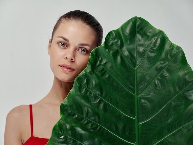 ヤシの木の緑の葉の近くの水着で魅力的な女性きれいな肌の自然な外観の若者