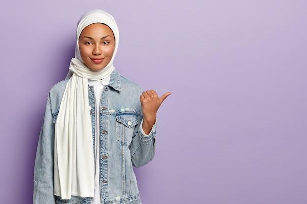 전통적인 아랍 의류에 매력적인 여자, 엄지 손가락을 오른쪽으로 가리키고, 빈 공간에 개체를 선물하고, 보라색 벽 위에 고립 된 종교적 견해를 가지고 있습니다. 종교 개념
