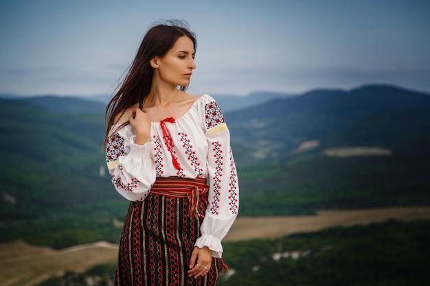 녹색 산 배경 흐리게에 전통적인 루마니아어 의상에서 매력적인 여자. 야외 사진. 전통과 문화적 다양성