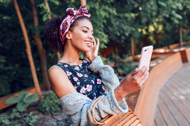 Привлекательная женщина в модном кардигане и повязке на голову, делая автопортрет