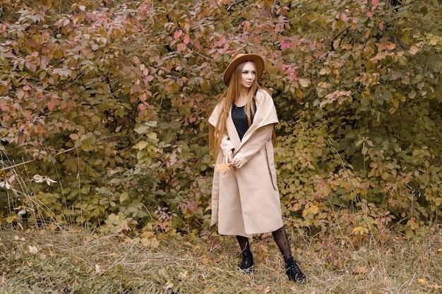 秋の背景に流行の服を着た魅力的な女性。秋にブログ。テキスト用の空き容量