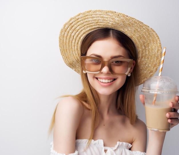 飲み物のポーズでトレンディな帽子グラスガラスの魅力的な女性