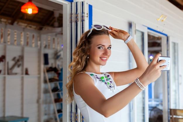 写真を撮る電話を使用してサングラスで夏のカフェで白いドレスの魅力的な女性