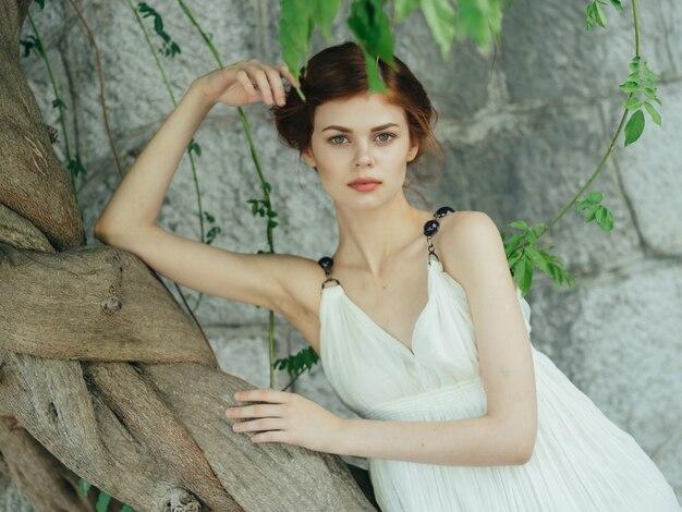 나무 기반 돌 벽 근처 흰 드레스에 매력적인 여자