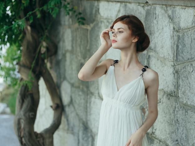 木の基礎の石の壁の近くに白いドレスを着た魅力的な女性