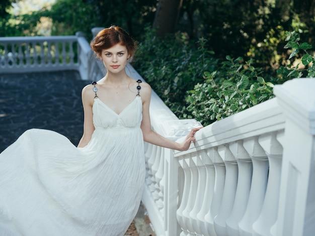 하얀 드레스를 입고 야외 장식 럭셔리 퀸을 걷는 매력적인 여자