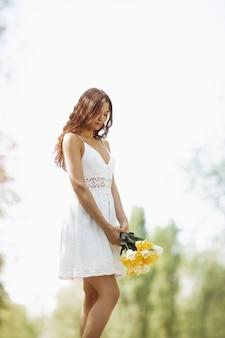 Привлекательная женщина в белом платье с букетом весенних цветов, стоящих на фоне боке природы