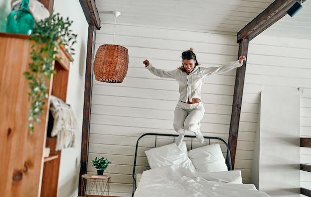 하얀 잠옷을 입은 매력적인 여성이 아침에 침대에서 즐겁게 뛰어놀고 있습니다.
