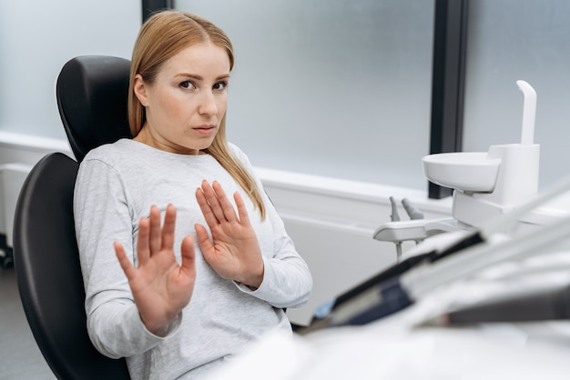 Attractive woman is afraid to treat teeth. a woman in the dental office shows a gesture so that no one comes