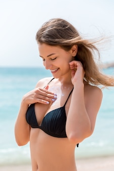 Attractive woman is applying sunblock on her breast with the fingers at the sea background.