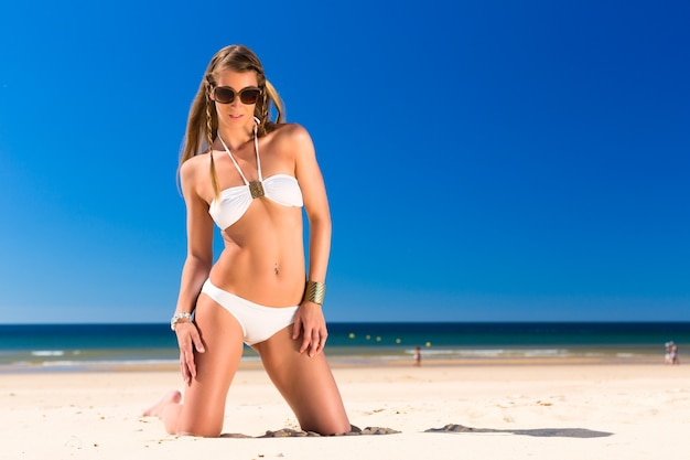 Attractive woman is kneeling  in the sun on beach