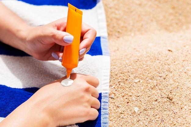 매력적인 여자는 해변에서 스트라이프 타월에 누워 그녀의 손에 튜브에서 자외선 차단제를 짜내고 있습니다.