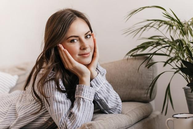 La donna attraente è sdraiata sul divano morbido, sporgendosi e guardando davanti