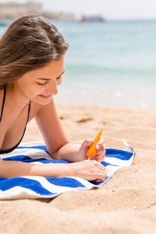 Attractive woman is lying on a striped towel at the beach and squeezing sunblock from a tube on her hand.